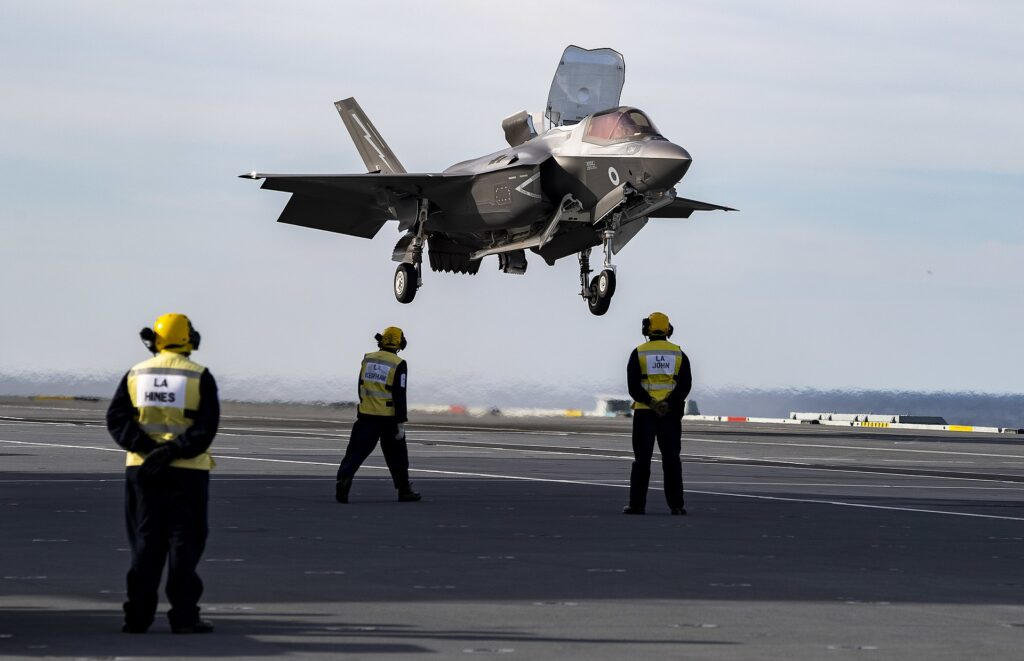 A Royal Air Force RAF F35B Lightning II performing a vertical landing on a Royal Navy carrier.